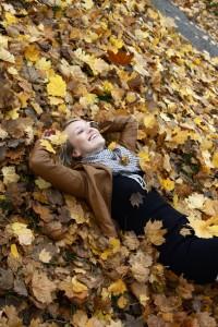 Frau mit brauner Lederjacke liegt im Laub